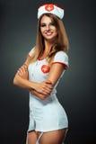 Bailarín joven y hermoso en el traje de la enfermera que presenta en estudio Imagenes de archivo