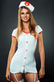 Bailarín joven y hermoso en el traje de la enfermera que presenta en estudio Foto de archivo libre de regalías