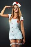 Bailarín joven y hermoso en el traje de la enfermera que presenta en estudio Imagen de archivo libre de regalías