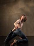 Bailarín moderno joven y elegante en fondo gris Imagen de archivo
