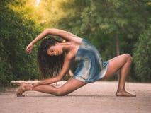 Bailarín que estira en el piso en un parque Fotos de archivo