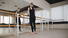 Bailar?n de la muchacha que calienta en el sal?n de baile en la barra del ballet almacen de metraje de vídeo