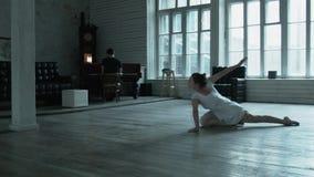 A bailarina é circundada belamente em um grande salão e suada na coluna No fundo um homem está jogando no filme