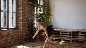 A bailarina adorável executa graciosamente o elemento do balé clássico em uma escola espaçoso moderna do bailado Tempo de treinam filme
