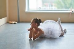 Bailarina adorável que encontra-se no assoalho Fotos de Stock Royalty Free