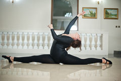 Bailarina agraciada que hace las fracturas en el piso de mármol Bailarín de ballet magnífico que realiza una fractura en piso bri Imagenes de archivo