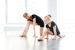 Bailarina alegre e professor pequenos que esticam na escola do bailado imagem de stock