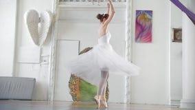 A bailarina atrativa nova no tutu branco executa a pirueta no estúdio espaçoso vídeos de arquivo