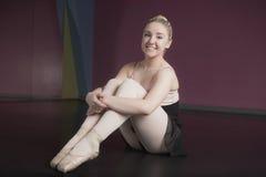 Bailarina bonita que se sienta y que sonríe en la cámara foto de archivo