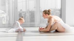Bailarina com a menina da criança que aquece-se antes de treinar fotografia de stock