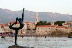 Bailarina da escultura (dançarino de Budva) contra o contexto da cidade velha fotografia de stock royalty free