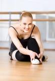 A bailarina de dobra estica-se no assoalho de madeira Fotos de Stock Royalty Free
