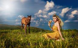 Bailarina de la danza del vientre de la mujer que se relaja en campo de hierba contra el cielo azul con las nubes blancas Fotos de archivo
