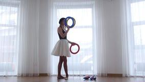 Bailarina de la mujer joven en sombrero negro que hace juegos malabares con los objetos de un círculo en estudio brillante por la metrajes