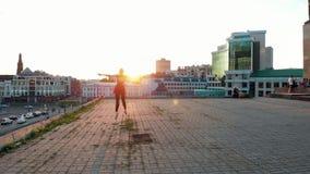 Bailarina de la mujer joven que entrena a su baile en el tejado - saltando y realizando fracturas - puesta del sol brillante almacen de video