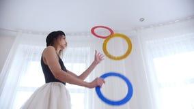 Bailarina de la mujer joven que hace juegos malabares con los objetos de un círculo en estudio brillante almacen de metraje de vídeo