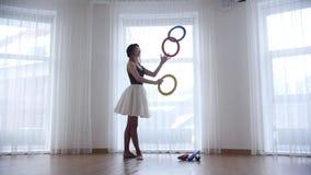 Bailarina de la mujer joven que hace juegos malabares con los objetos de un círculo en estudio brillante por la ventana almacen de metraje de vídeo