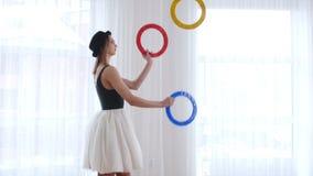 Bailarina de la mujer joven que hace juegos malabares con los objetos de un círculo metrajes