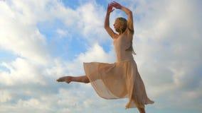Bailarina de salto en vestido de seda beige y pointe en fondo del cielo Silueta de la mujer rubia hermosa joven con de largo almacen de metraje de vídeo