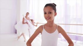 A bailarina de sorriso da criança está olhando a câmera Professor com a menina no fundo vídeos de arquivo