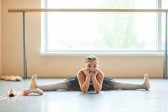Bailarina de sorriso que senta-se na separação no estúdio Fotografia de Stock Royalty Free