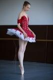 Bailarina delgada que se coloca en pointe en el salón de baile que mira abajo Imagen de archivo libre de regalías