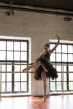 Bailarina do ensaio no sal?o Assoalho de madeira, grandes janelas Bailarina bonita na sala do ensaio imagens de stock