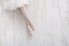 Bailarina em sapatas do pointe, pés graciosos, fundo do bailado Imagens de Stock Royalty Free