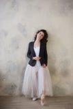 Bailarina em um maiô branco e da saia longa com um corpo bonito que está em sapatas do pointe imagens de stock