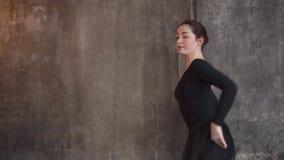 A bailarina em uma classe de treinamento está ensaiando etapas de dança e entrega posições video estoque