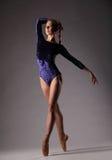 Bailarina en el equipo azul que presenta en los dedos del pie, fondo gris del estudio foto de archivo libre de regalías