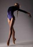Bailarina en el equipo azul que presenta en los dedos del pie, fondo gris del estudio irreconocible fotografía de archivo