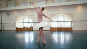 Bailarina en el vestido blanco del tutú del ballet que practica en estudio o gimnasio de la danza Mujer que baila pas clásico en  almacen de metraje de vídeo