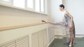 Bailarina en el vestido de la etapa que estira la pierna en fractura vertical cerca de ventana en clase almacen de metraje de vídeo