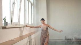 Bailarina en el vestido que vuela que dobla su pierna que se prepara al funcionamiento en etapa almacen de metraje de vídeo