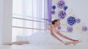 Bailarina en los estiramientos blancos del tutú y de los pointes que se sientan en la guita en clase del ballet almacen de video