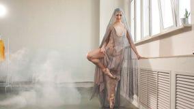 Bailarina en vestido escénico de la gasa airosa que se resuelve en pasillo vacío almacen de metraje de vídeo