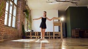 Bailarina encantador nova no terno preto que pratica na pirueta no estúdio da dança Clássico magro bonito da dança da menina filme