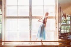 A bailarina está dançando na frente de uma grande janela Foto de Stock Royalty Free
