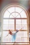 A bailarina está dançando na frente de uma grande janela Fotografia de Stock