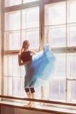A bailarina está dançando na frente de uma grande janela Fotos de Stock Royalty Free