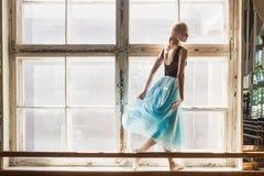 A bailarina está dançando na frente de uma grande janela Foto de Stock