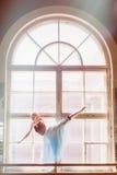 A bailarina está dançando na frente de uma grande janela Fotografia de Stock Royalty Free