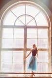 A bailarina está levantando na frente de uma grande janela Fotos de Stock Royalty Free