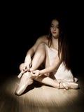 Bailarina hermosa de la mujer joven que ata los zapatos del pointe en un fondo oscuro Foto de archivo libre de regalías