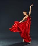 Bailarina hermosa que baila un vuelo rojo largo del vestido Foto de archivo