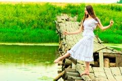 Bailarina hermosa que equilibra en el puente por el río Fotos de archivo