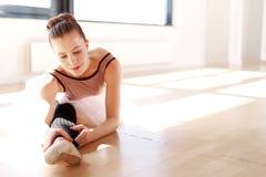 Bailarina joven que estira la pierna en Sunny Studio Fotos de archivo