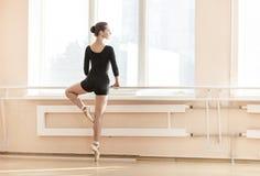 Bailarina joven que se coloca en poite en la barra Imagen de archivo