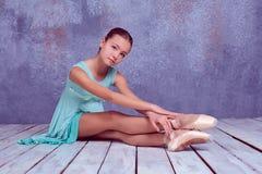Bailarina joven que se sienta en piso de madera Fotografía de archivo libre de regalías